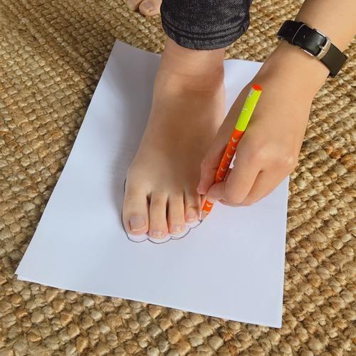 在白紙上沿著腳板的輪廓畫出腳型(圖片來源:FMshoes)